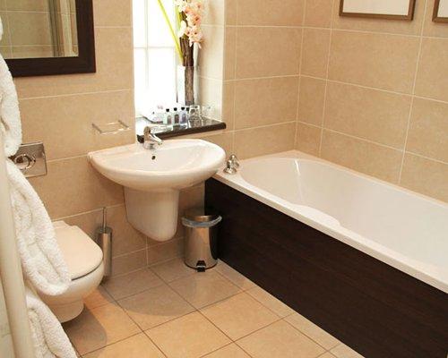A bathroom with single sink vanity bathtub and shower.