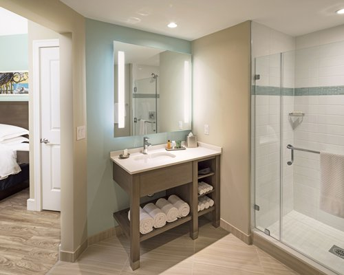 A bathroom with shower stall and open sink vanity alongside the bedroom.