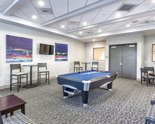 An indoor recreation room with a pool table and television.