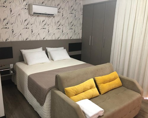 A bedroom with a large bed and sofa sitting area with storage closet.