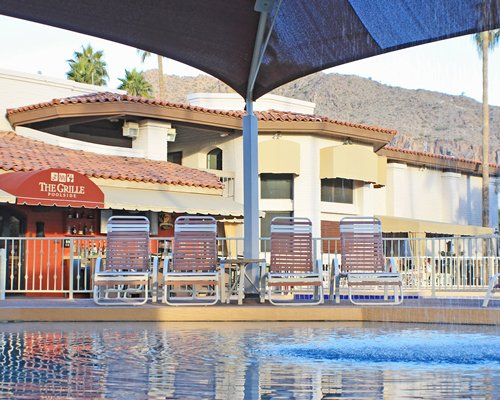 An outdoor swimming pool with chaise lounge chairs and sunshades alongside the resort unit.