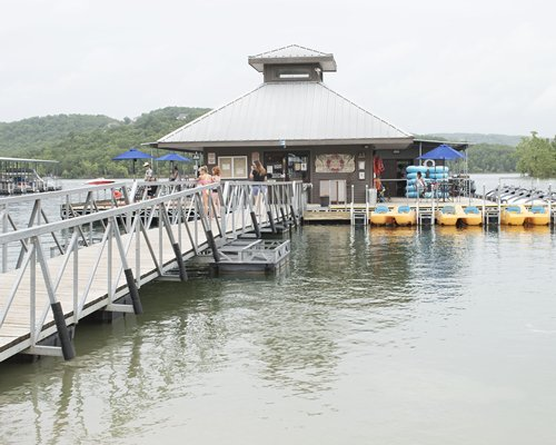 A pier leading to a marina on the lake surrounded by wooded area.