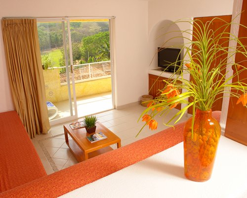 A well furnished living room with a television and balcony.
