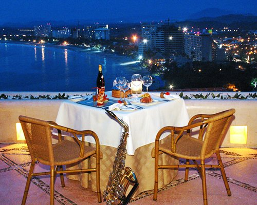 An outdoor dining area alongside the ocean at night.
