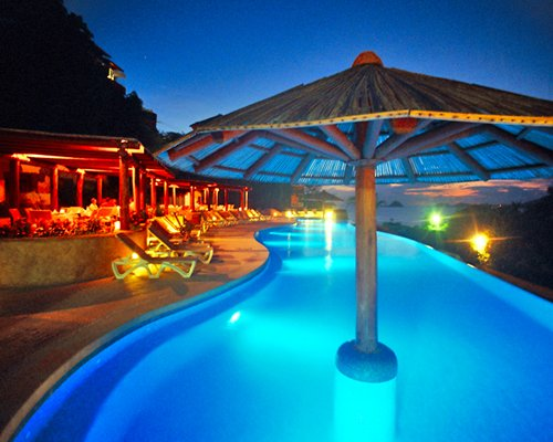An outdoor swimming pool with a thatched roof and chaise lounge chairs at night.