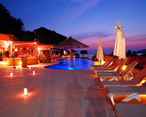 An outdoor swimming pool with chaise lounge chairs and sunshades alongside the resort at night.