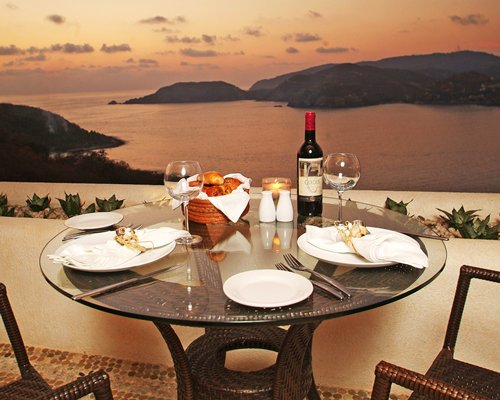A balcony dining area alongside the ocean and the mountains.
