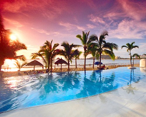 Large outdoor swimming pool alongside the ocean with chaise lounge chairs thatched sunshades and palm trees.
