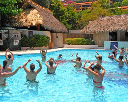 A group of people doing exercise in an outdoor swimming pool alongside the resort unit.