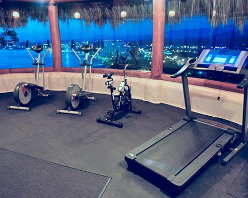 A well equipped indoor fitness center with outside view.