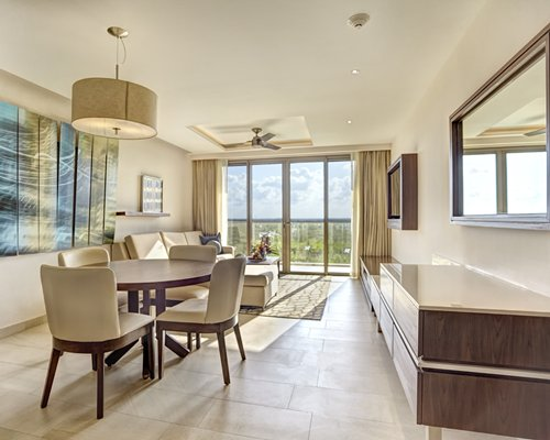A well furnished open plan living room, dining area and balcony.