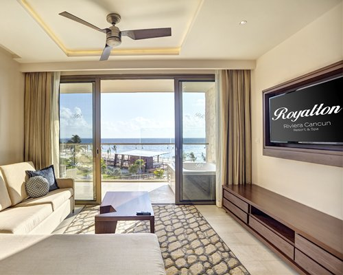 A well furnished living room with sofa, television and a balcony with a hot tub.