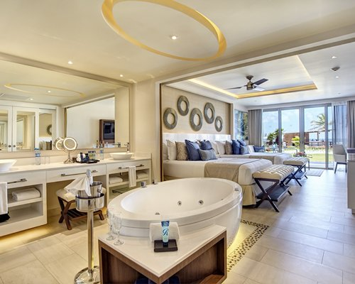 A well furnished bedroom with two twin beds, bathtub, double open sink vanity, and outside view.