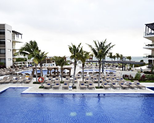 An outdoor swimming pool with chaise lounge chairs and cabana alongside resort units.