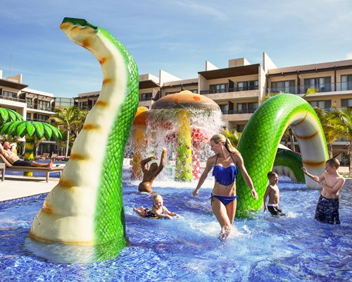 Guests playing in outdoor water park with serpent and raining mushroom umbrella.