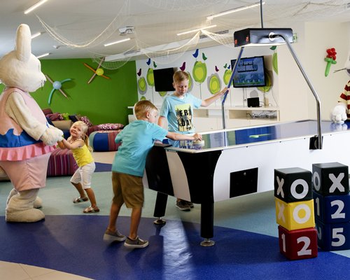 Kids play area with children, mascot, air hockey table, and television.