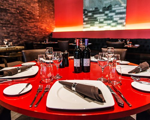 A fine dining restaurant with close-up of dining table, plates, wine, and glasses.