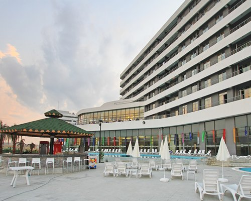 An exterior view of resort and outdoor bar with pools and patio seating at dusk.