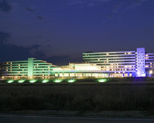 An exterior view of resort with lights at night.