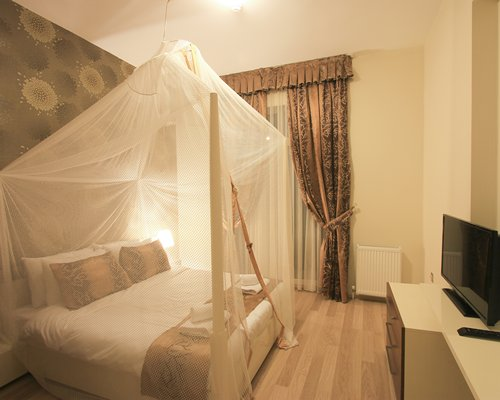 A well furnished bedroom with double bed and a television.