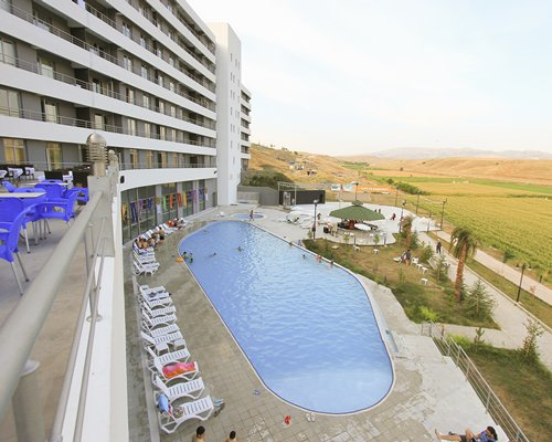 An outdoor swimming pool with chaise lounge chairs and sunshades alongside the multi story resort unit.