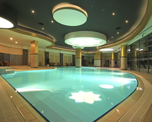 An indoor swimming pool with a patio furniture.