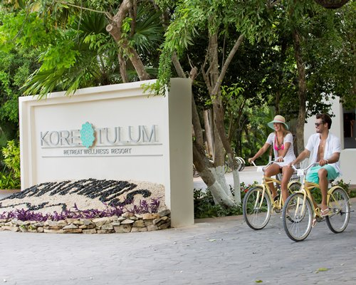A couple cycling alongside a signboard of Kore Tulum Retreat and Spa Resort.