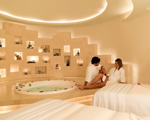 A couple in an indoor spa with a bathtub.