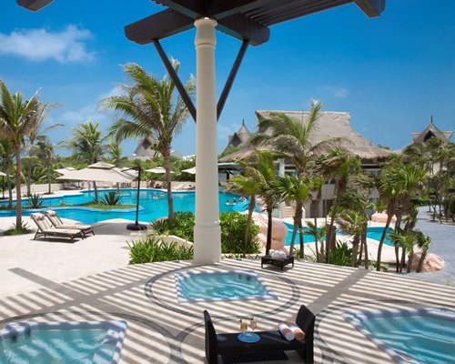 An outdoor swimming pool with sunshades chaise lounge chairs and landscaping alongside the resort.