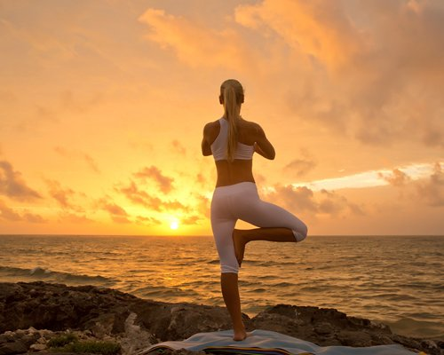 A woman performing yoga during the sunrise.
