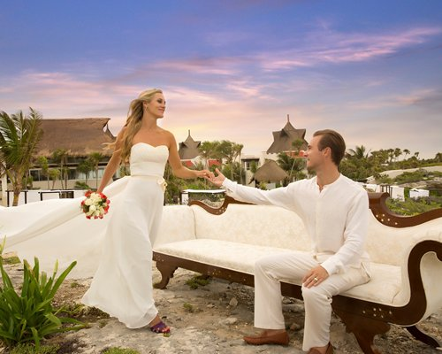 A wedding couple sitting in an outdoor lounge chair at the resort.