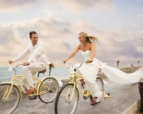 Couple riding bikes on a pier along the sea.