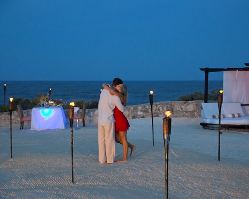 A couple in the outdoor dining area alongside the beach beds at night.