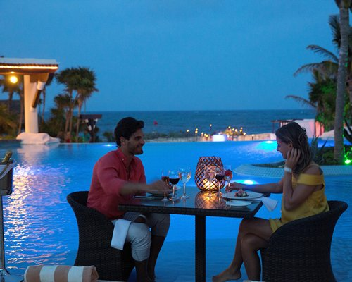 A couple in the outdoor dining area alongside the swimming pool at night.