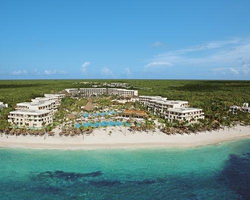 The Secrets Akumal Riviera Maya Resort with an outdoor swimming pool and white sand beach.