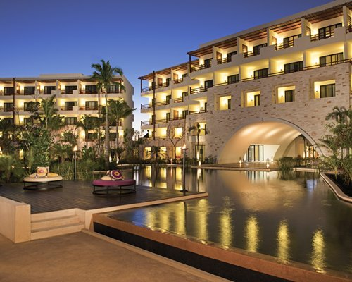An outdoor swimming pool with garden furniture alongside the multi story resort unit.