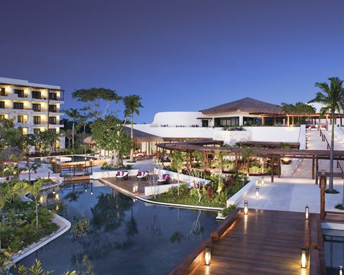 An outdoor swimming pool with garden furniture and landscaping alongside the resort units at dusk.
