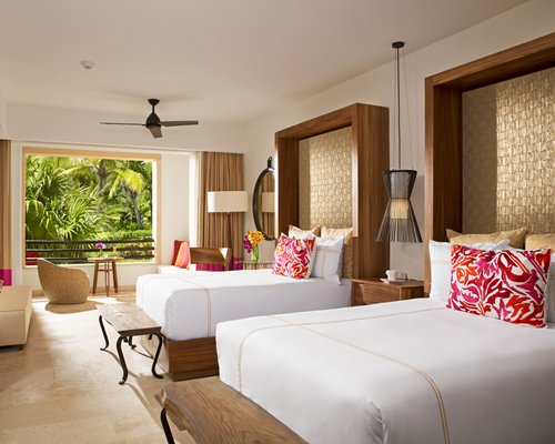 A well furnished bedroom with two beds and balcony.