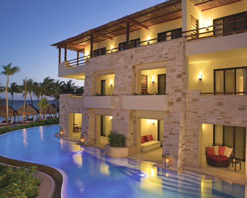 An exterior view of the multi story resort balconies alongside the outdoor swimming pool at night.