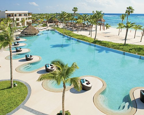 An outdoor swimming pool alongside the sea and resort units.