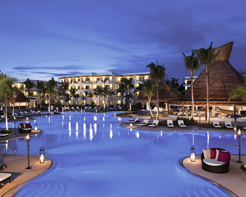 Large outdoor swimming pool alongside the resort at dusk.