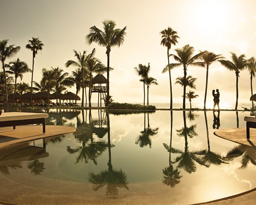 A couple enjoying the sunset by the outdoor pool and palm trees.