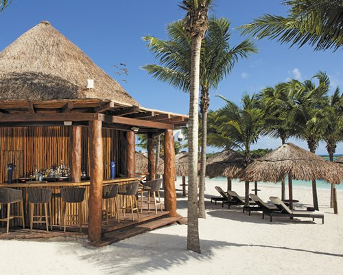 A view of the poolside bar with chaise lounge chairs and thatched sunshades alongside the sea.