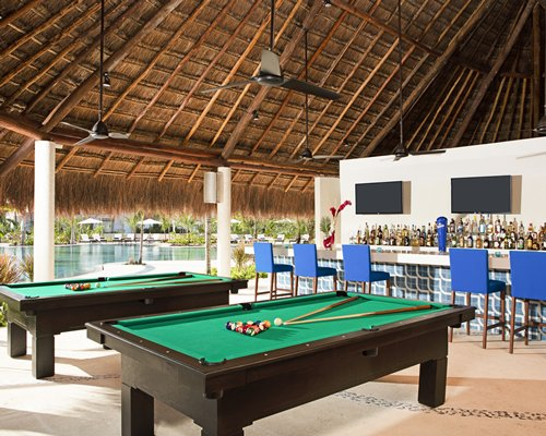 Covered bar with pool tables alongside an outdoor swimming pool.