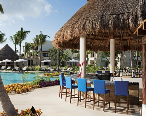 An outdoor swimming pools with chaise lounge chairs and sunshades alongside a poolside bar.