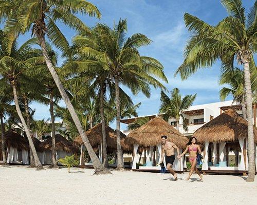 A couple at the beach alongside a cabana and coconut trees.