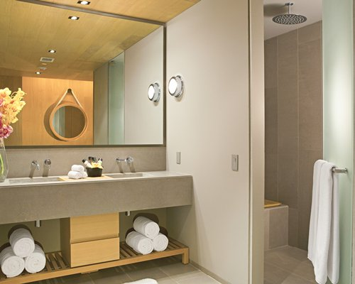 A bathroom with a standup shower and double sink vanity.