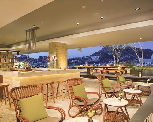 An indoor bar at the resort with an outside view.