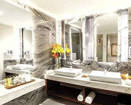 A bathroom with double sink vanity and stand up shower.