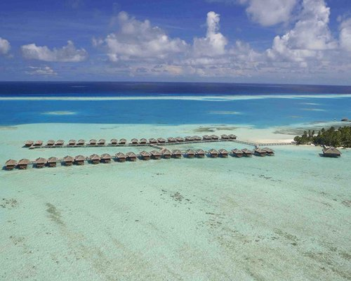 Exterior view of multiple units at Medhufushi Island Resort alongside the ocean.